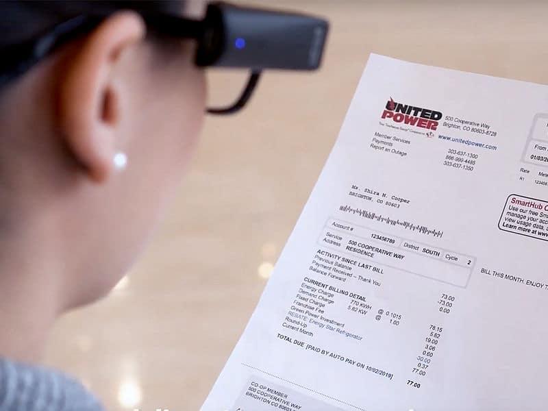 Eine Frau läßt sich eine Rechnung von der OrCam vorlesen