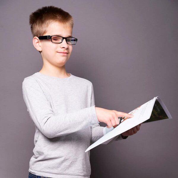 OrCam Kind läst sich ein Buch vorlesen