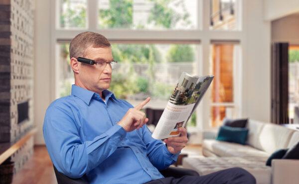 OrCam Mann liest Zeitschrift per Fingerzeig